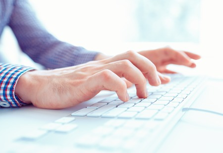 Photo pour Male hands or men office worker typing on the keyboard - image libre de droit