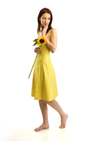 Young girl in yellov dress holding a sunflower
