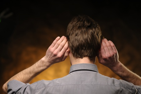 Man in shirt from behind with hands on ears