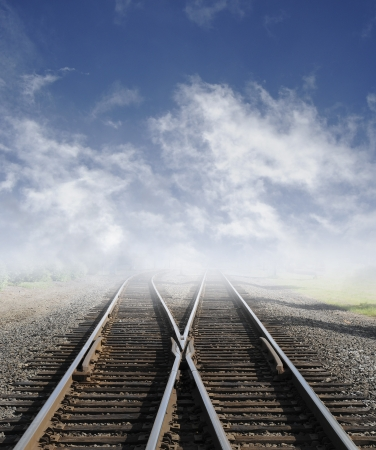 Two railroad tracks lead off into the daylight foggy sky with clouds.