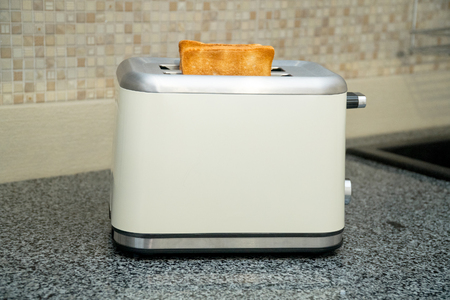Photo for Toaster with toasted bread for breakfast inside. Gray table - Royalty Free Image