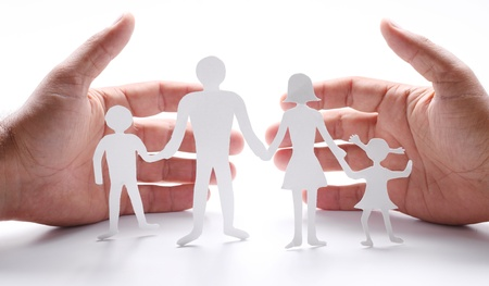 Foto de Cardboard figures of the family on a white background. The symbol of unity and happiness. Hands gently hug the family. - Imagen libre de derechos