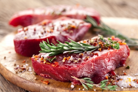 Raw beef steak on a dark wooden table