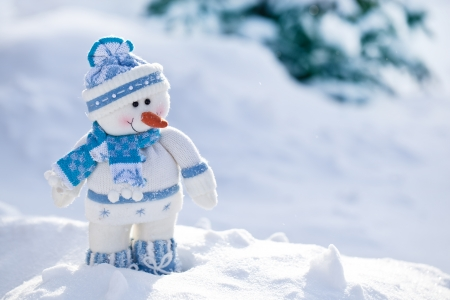 Foto de Little snowman with carrot nose in the snow. - Imagen libre de derechos