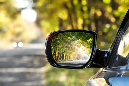 Photo for Reflection of  sunny autumn road at the car side mirrow. - Royalty Free Image