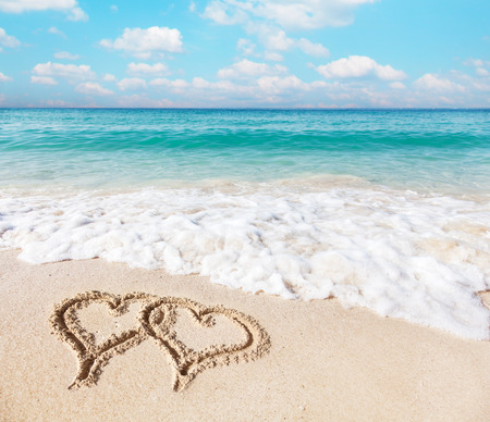 Photo pour Hearts drawn on the beach sand. - image libre de droit