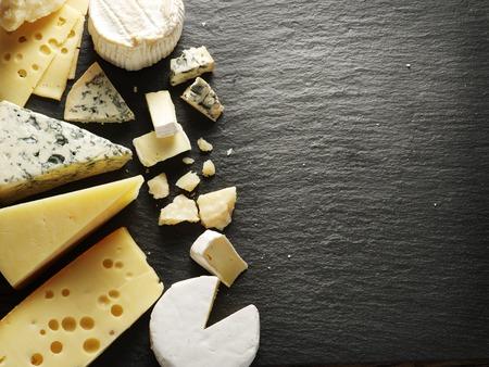 Foto de Different types of cheeses on black board. - Imagen libre de derechos