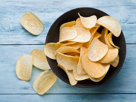 Photo pour Potato chips on a blue wooden background. - image libre de droit