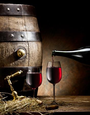 Foto de Stilllife with glass of wine bottle and barrel on the table in the cellar. - Imagen libre de derechos