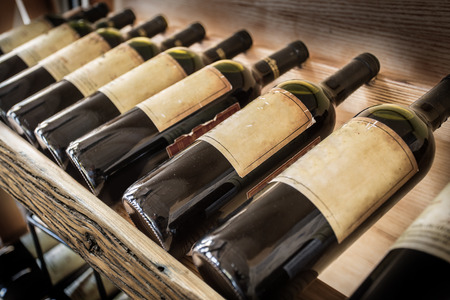 Photo pour Old wine bottles on the wine shelf. - image libre de droit