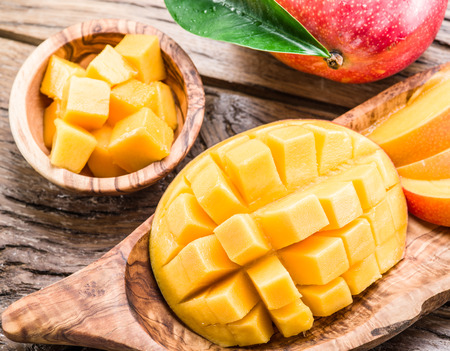 Foto de Mango fruit and mango cubes on the wooden table. - Imagen libre de derechos