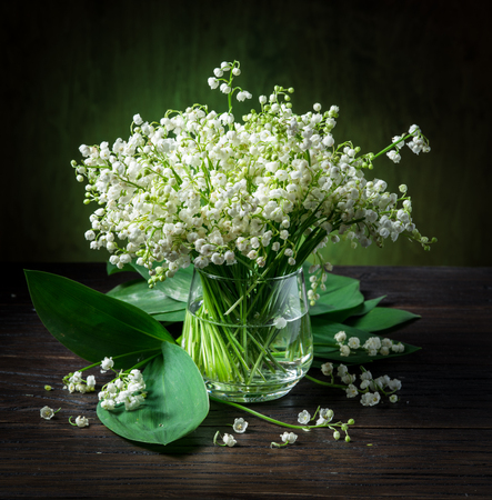 Photo pour Lily of the valley bouquet on the wooden table. - image libre de droit