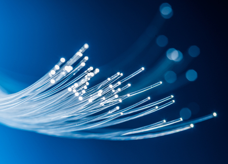 Foto de Bundle of optical fibers with lights in the ends. Blue background. - Imagen libre de derechos