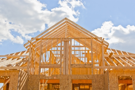 Photo pour New residential construction home framing against a blue sky - image libre de droit