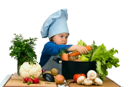 Photo for Cute little girl cooking soup with lots of different vegetables - Royalty Free Image