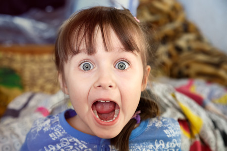 Photo pour Shocked screaming little girl with opened mouth in her bedroom - image libre de droit