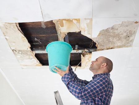 Foto de Man Collecting Water In Bucket From Ceiling. Ceiling panels damaged - Imagen libre de derechos