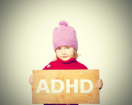 Foto de Little girl holding Board with inscription ADHD. Isolated on white background - Imagen libre de derechos