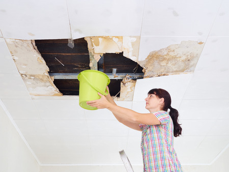 Photo pour Young Woman Collecting Water In Bucket From Ceiling. Ceiling panels damaged huge hole in roof from rainwater leakage.Water damaged ceiling . - image libre de droit