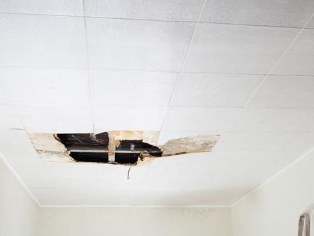 Foto de Ceiling panels damaged  huge hole in roof from rainwater leakage.Water damaged ceiling . - Imagen libre de derechos