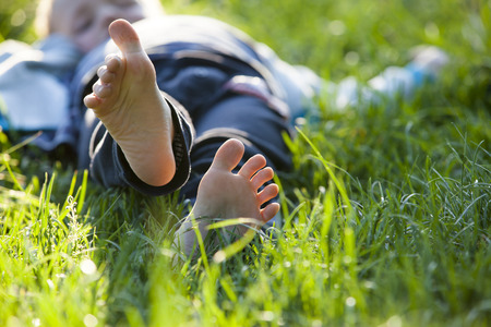 Photo for Happy little boy lying on green grass outdoors in spring park. - Royalty Free Image