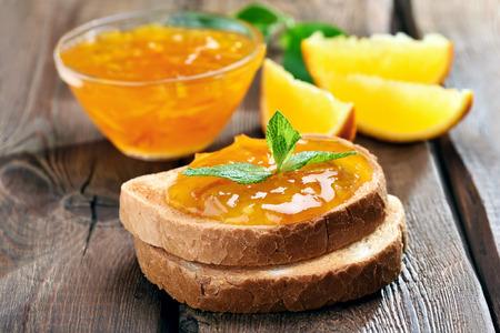 Foto de Bread and orange homemade jam on wooden table, close up view - Imagen libre de derechos