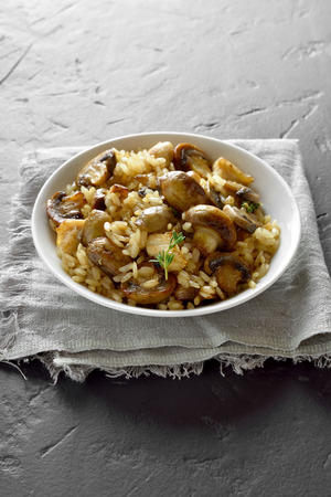 Foto de Risotto with mushrooms and pieces of chicken meat on black stone background with copy space.  - Imagen libre de derechos