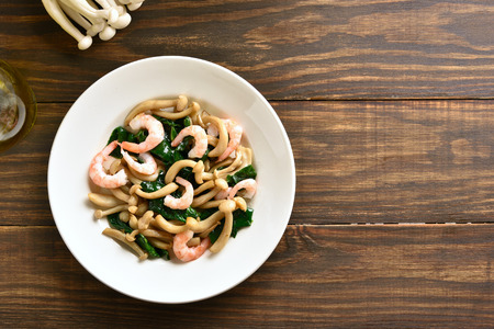 Photo for Asian style stir-fried white beech mushrooms with leaves of spinach and shrimps on plate over on wooden background with copy space. Top view, flat lay - Royalty Free Image