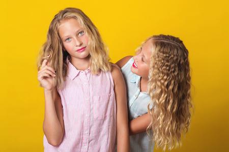 Foto de Funny girls twins have fun together on the yellow background. - Imagen libre de derechos