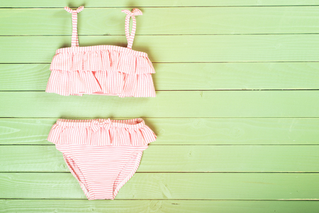 Photo for Little girl's swimsuit on the wooden background. Top view. Space for text. - Royalty Free Image
