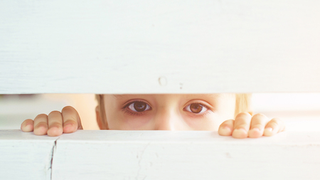 Photo for Frightened child is spying through a wooden fence. Scared child boy. Human emotion, facial expression. Sad kid outdoors. Bored little boy - Royalty Free Image