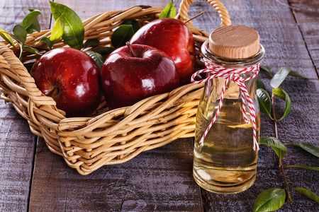 Foto per Apple cider vinegar and red apples over rustic wooden background - Immagine Royalty Free