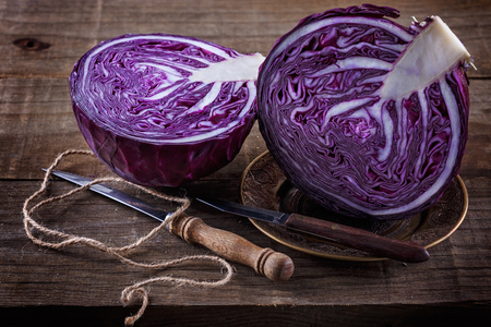 Photo pour Head of Red cabbage cut in half and knives over rustic wooden background - image libre de droit