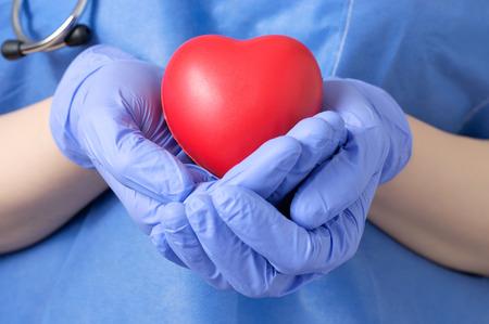 Foto de Female doctor holding a red heart shape - Imagen libre de derechos