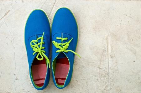 pair of blue sneaker on textured cement floor