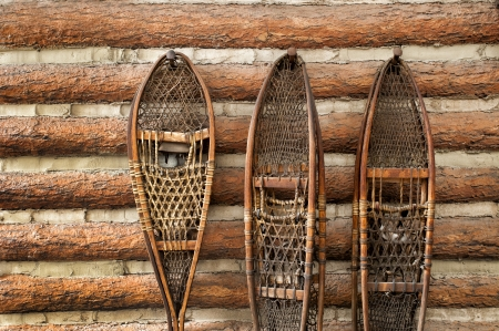 pair of vintage snow shoes hanging on a cabin