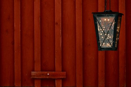 Foto de Old vintage lantern with vintage garland light inside at the rural red wooden wall. Christmas vacation decorations concept with a copy space for text. - Imagen libre de derechos