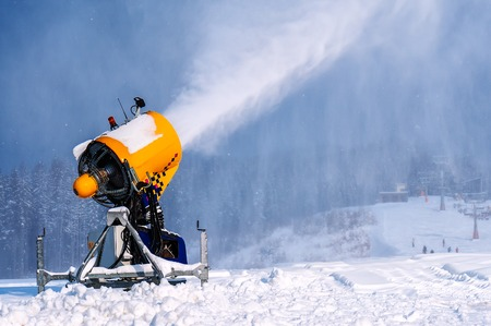Foto de professional artificial snow machine cannon making snowflakes from water at ski resort - Imagen libre de derechos