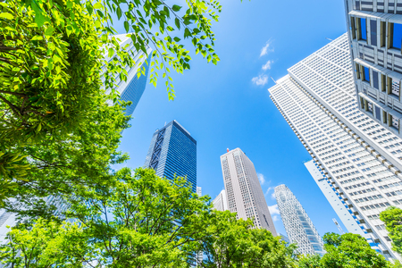 Foto de Asia Business concept for real estate, corporate construction and ecology - looking up view of panoramic modern city skyline with blue sky and green tree in shinjuku, tokyo, japan - Imagen libre de derechos