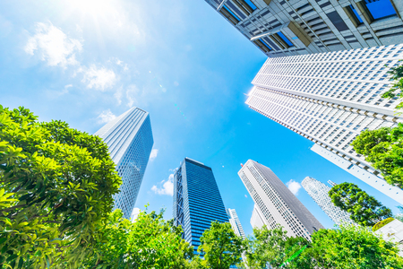 Photo for Asia Business concept for real estate, corporate construction and ecology - looking up view of panoramic modern city skyline with blue sky and green tree in shinjuku, tokyo, japan - Royalty Free Image