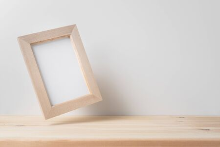 Design concept - front view of vertical wood photo frame on wood floor and mid air with white wall for mockup, real photo, not 3D render