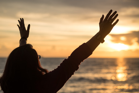 Photo pour Silhouette image of a woman raising hands towards heaven in sun set time - image libre de droit