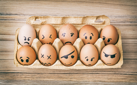 Emotion face painted eggs in paper box. Funny drawing faces.