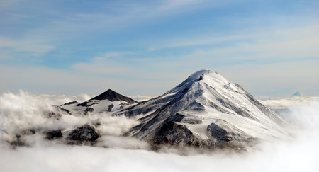 Foto de peaks of mountains above the clouds, Russia, Kamchatka - Imagen libre de derechos
