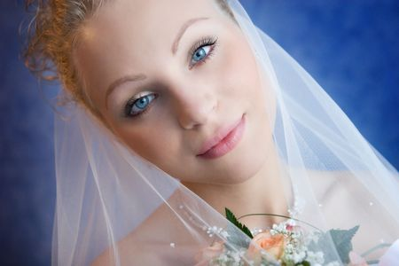 The bride holds a bouquet and pensively looks