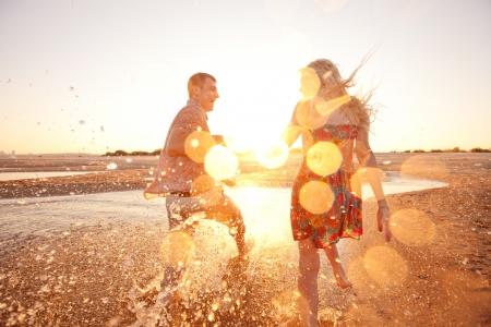 happy couple running on the beach