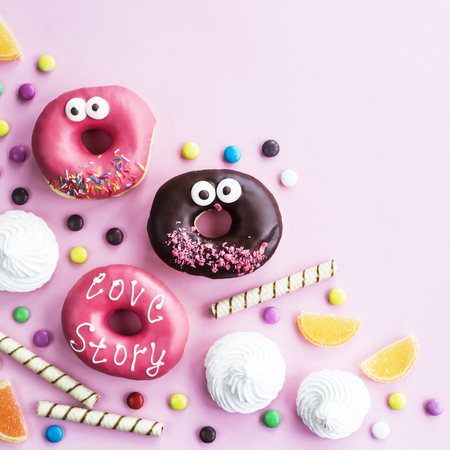 Photo for Junk food. Donuts, marmalade, chocolate sticks and balls, and meringue on a pink background. Unhealthy food concept. Top view. Copyspace - Royalty Free Image