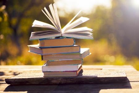Foto de Open book on wooden table on natural background. Soft focus - Imagen libre de derechos