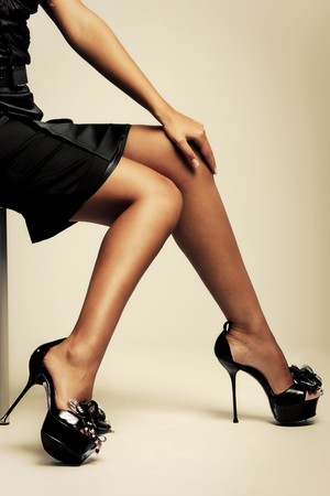 beautiful tanned female lags in high heels, studio shot