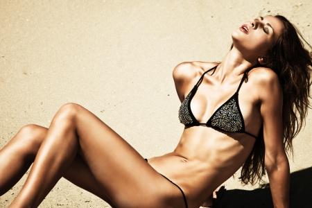 attractive woman in bikini, outdoor shot in sand, summer day